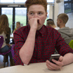 Cropped image of a stressed schoolboy sitting away from people at school. He has a smartphone in his hand and is looking away with his hand to his face.