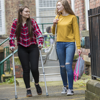 A young woman helps her friend who is on crutches by providing support and carrying her bag.