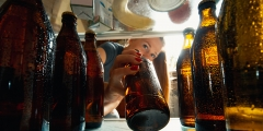Young woman takes cold refreshing beer from out the fridge, inside view from fridge of hand holding the bottle.