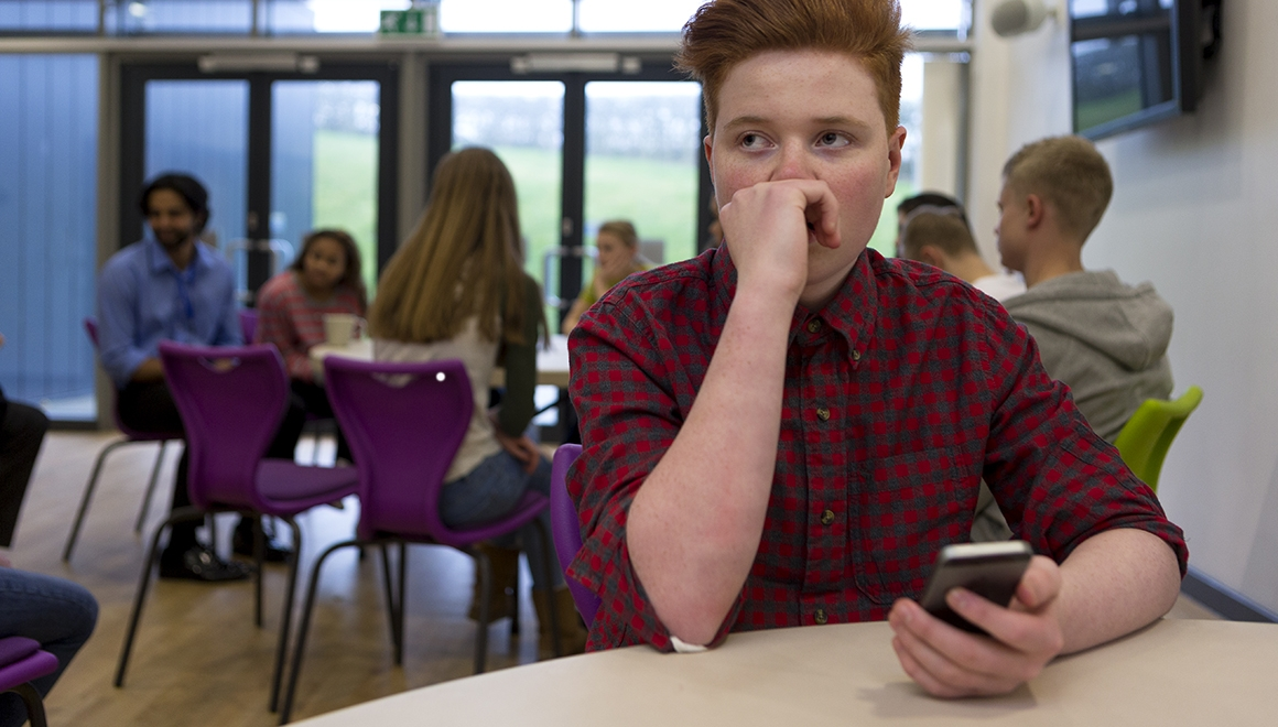 Stressed schoolboy sitting away from people at school. He has a smartphone in his hand and is looking away with his hand to his face.