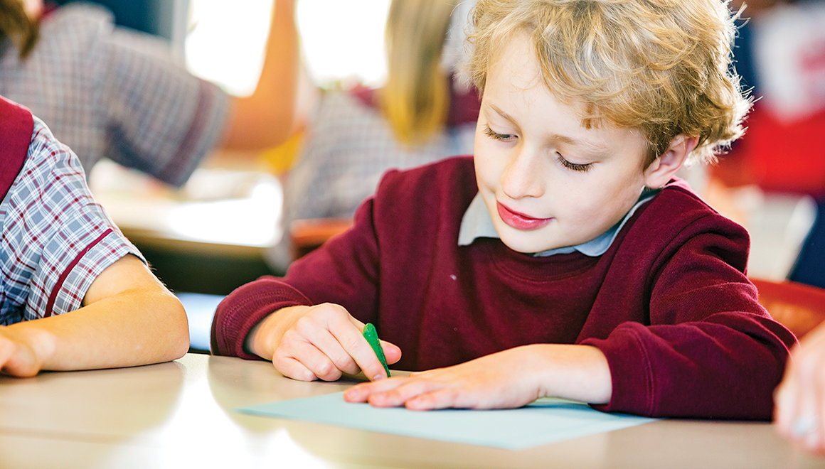 A young schoolboy drawing on a piece of paper