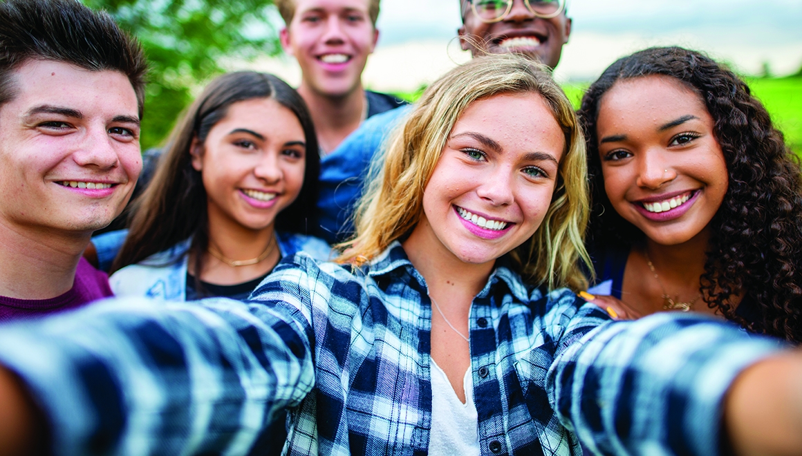A multi-ethnic group of high school students are outdoors on a summer day. One girl is taking a selfie with the group.