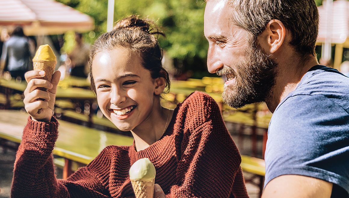 Happy father and daughter eating ice cream outdoors
