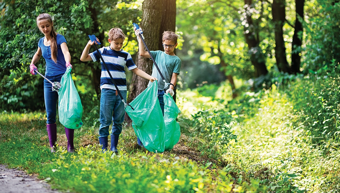 Group of teens, cleaning together in public park, saving the environment.