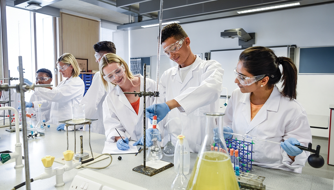 Young people using scientific apparatus, young man adjusting chemical flask on clamp with tall glass tube, two young women smiling and watching