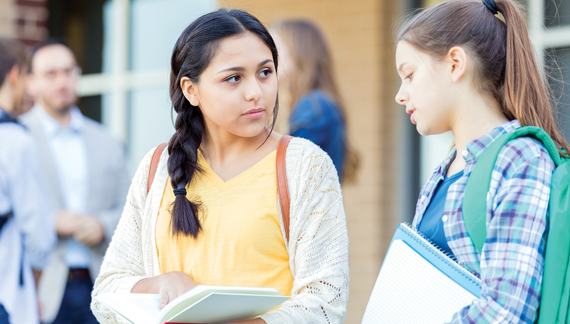 Serious teenage girls discuss an upcoming exam as they wait for school to start