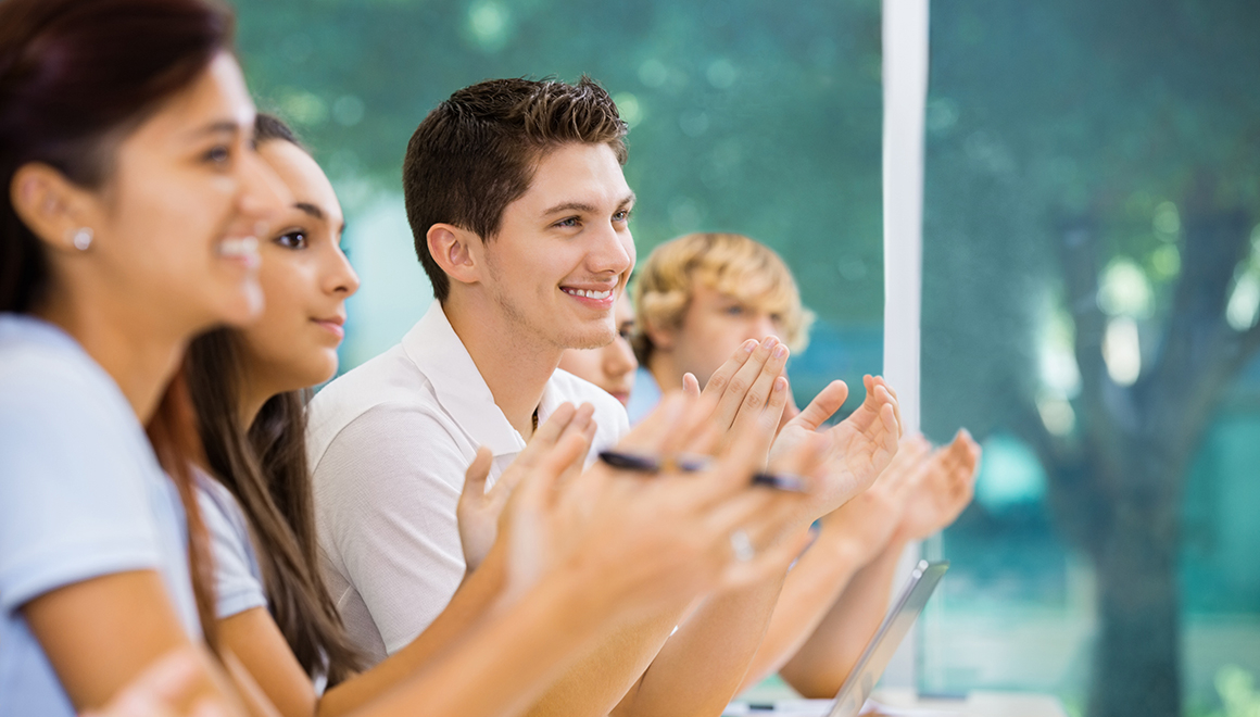 Teen students applauding during lecture at private school