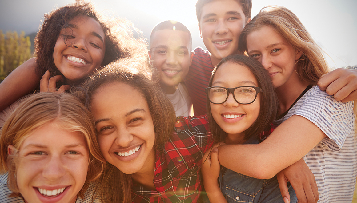 A group of teenagers smiling down at a camera from above