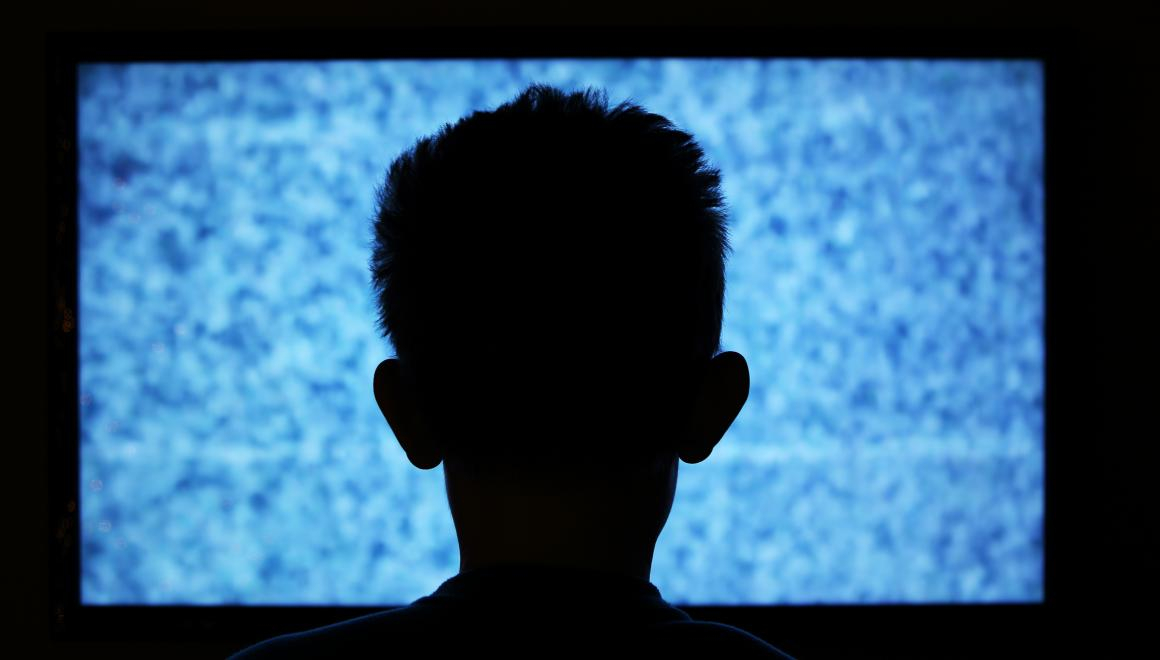 A silhouette of a child sitting infront of a screen